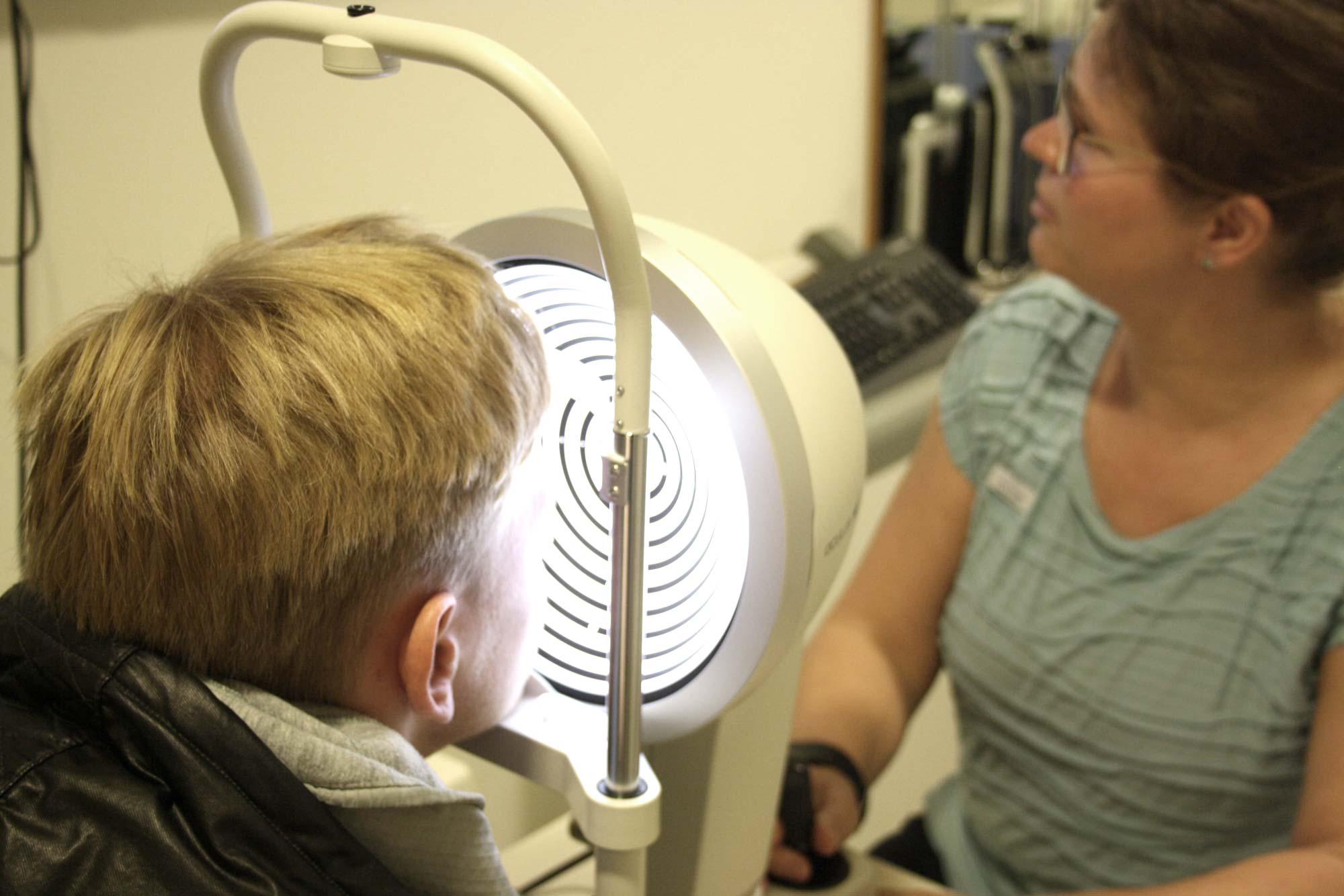 F.C. Hansa Spieler Willi Evseev lässt sich von Kontaktlinsenspezialistin Anja Stengel mit dem Oculus Keratographen 5M die Augen überprüfen - bei Optik Sagawe in Rostock